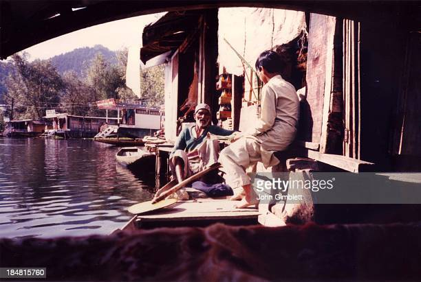 CONTENT] An old man and a boy with their shakara sit resting near houseboats on Dal Lake waiting for customers