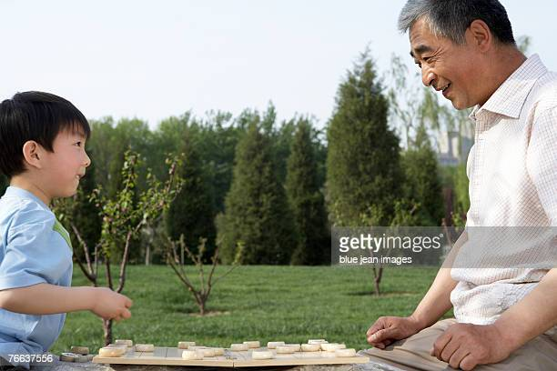 An old man and a little boy are playing Chinese chess.
