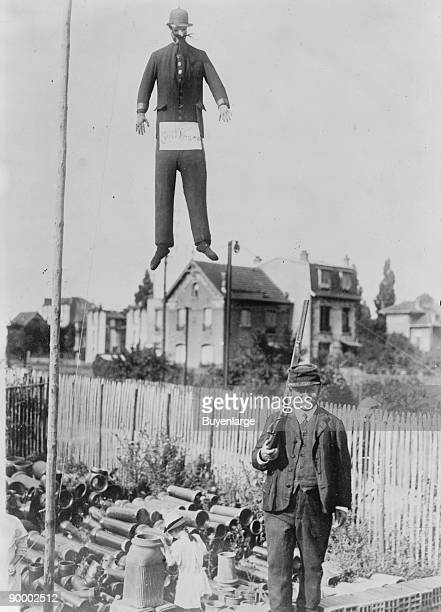 An old man carrying a rifle guards a hanging effigy of Kaiser Wilhelm of Germany