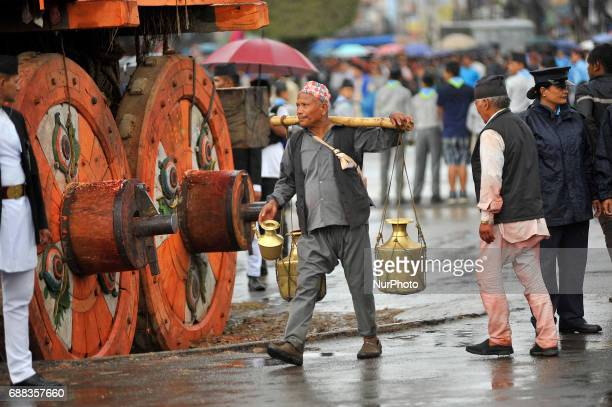 An old man distributing driking water during celebration of Bhoto Jatra festival at Jawalakhel Patan Nepal on Thursday May 25 2017 Rato Machindranath...