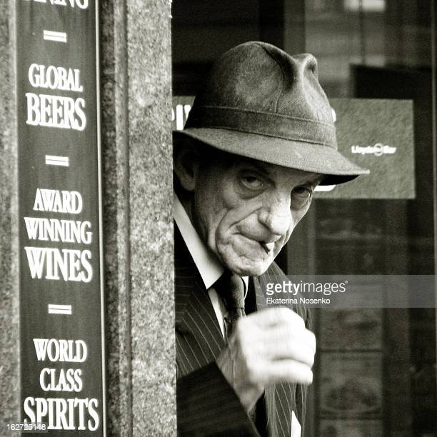 An old man dressed in old fashion manner with in a suite with a tie and a fedora hat is enjoying a cigarette outside a pub in Bexleyheath, Kent....