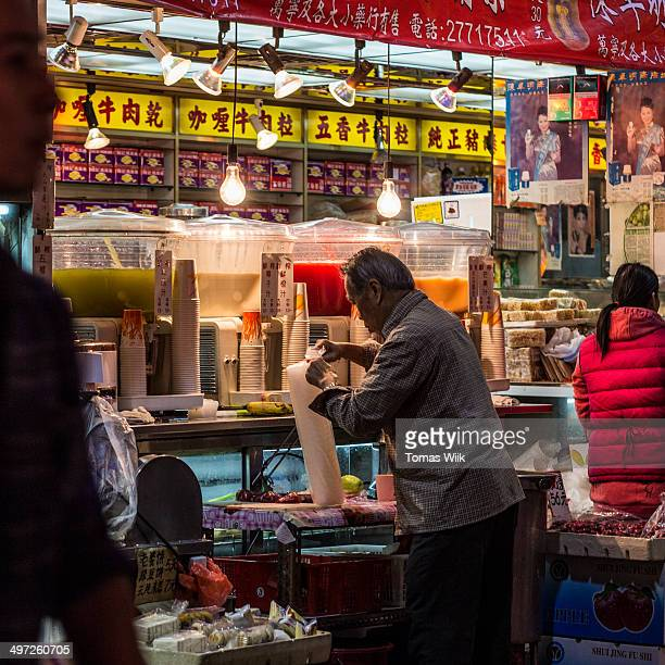 An old man handling empty cup lids outside a sharply lit juice booth in Yau Ma Tei, Hong Kong, China.