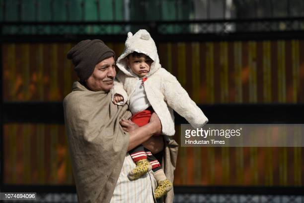An old man holds a child as they wear warm clothes to protect themselves from cold on a winter morning at Mahadev road on December 23 2018 in New...