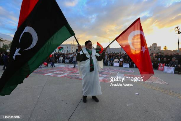 An old man holds flags of Turkey and Libya during a demonstration against eastern military commander Khalifa Haftar, who is based in the east of the...