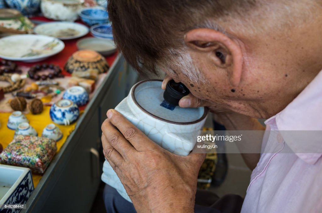 An Old Man Identifying Porcelain Pottery With Magnifying Lens In