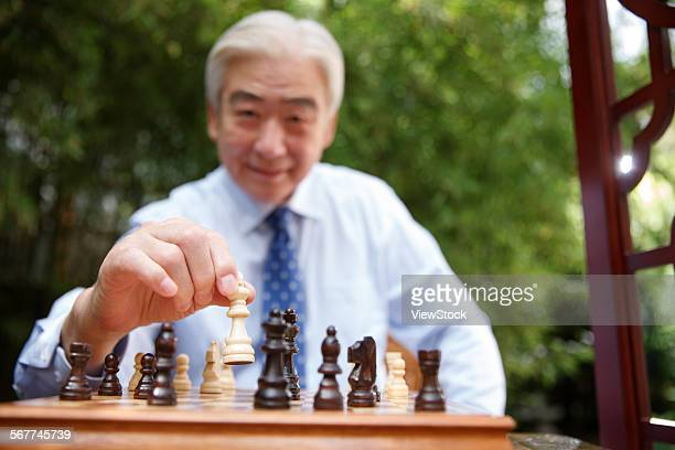 An old man in chess in the yard