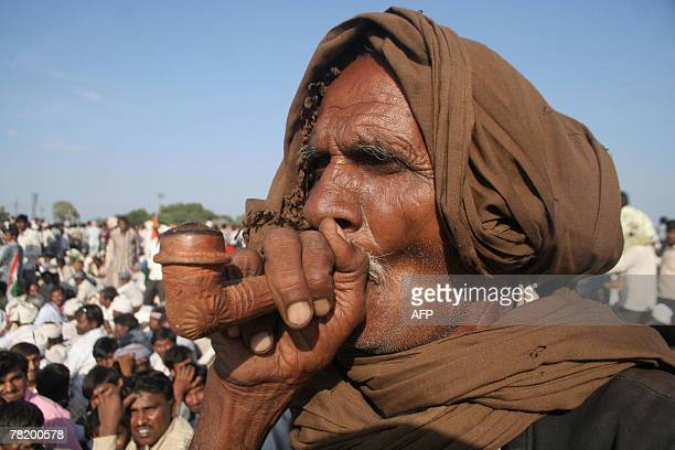 An old man in his traditional attire puffs a Hookah while listening to Congress Party president Sonia Gandhi during a public meeting at Jasdan town,...