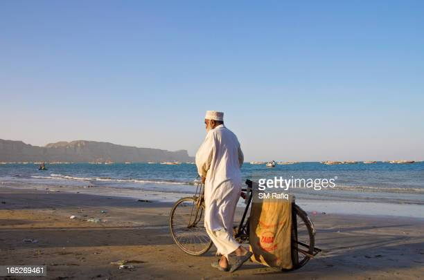 An old man is walking with cycle along sea.