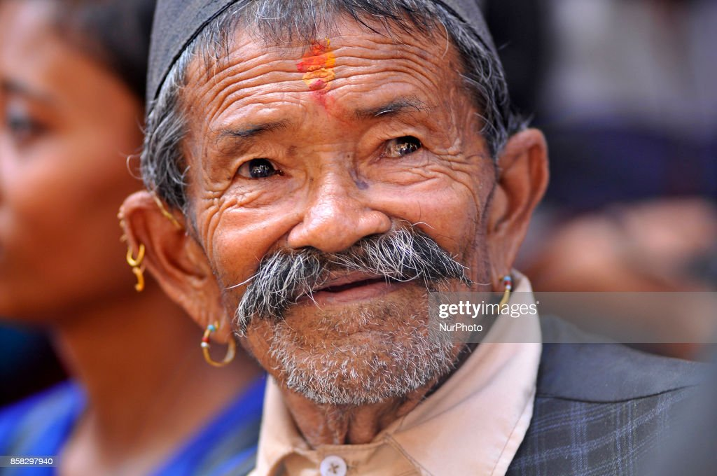 An old man observing festival as Locals carry as well as rotates top part of a chariot of Lord Narayan across the streets of Hadigaun during Lord Narayan jatra festival in Hadigaun, Kathmandu, Nepal on Friday, October 06, 2017. Once in a every year right after Dashain Festival this festival celebrates. The Narayan Jatra Festival of Hadigaun is a unique Festival in the capital involving three circular bamboo structures, above which an idol of the Lord Narayan in placed, and then rotated by two people standing below.