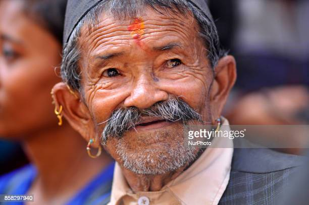 An old man observing festival as Locals carry as well as rotates top part of a chariot of Lord Narayan across the streets of Hadigaun during Lord...