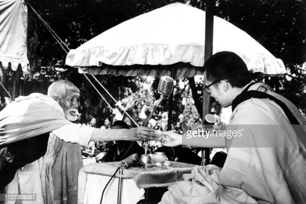 An old man offers a wild flower to Dalai Lama the traditional religious and temporal head of Tibet's Buddhist clergy seating under a canopy as he...