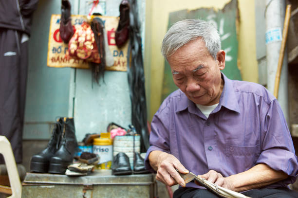 an old man on the side of the street who fixes old shoes - old asian shoe maker stock pictures, royalty-free photos & images
