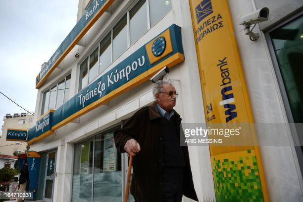 An old man passes by a Bank of Cyprus branch in Athens on March 27 as Greek subsidiaries of three Cypriot banks reopened today after Greece's third...