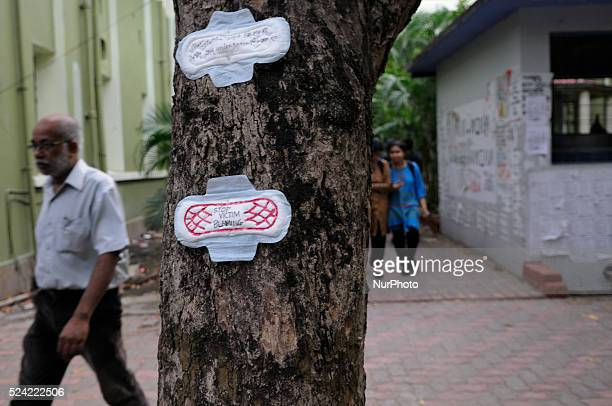 An old man passing by a tree which has anti sexism messages written on sanitary napkins during a Sanitary napkin protest in Kolkata, India.