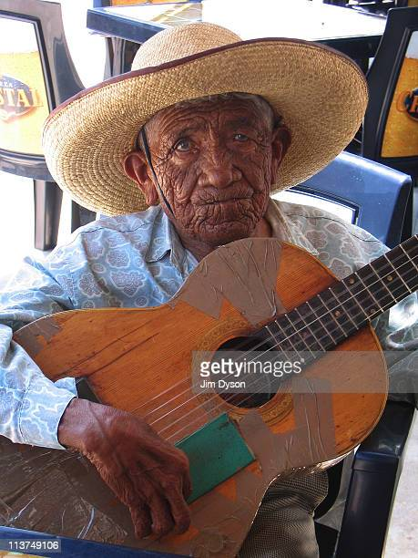 An old man plays the guitar at a cafe near the Ballestas islands on March 8 2005 near Pisco Peru