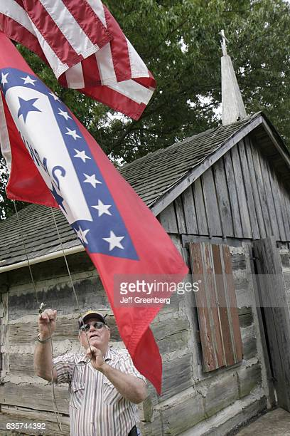 An old man raises flags outside a log church in Maynard Pioneer Museum and Park