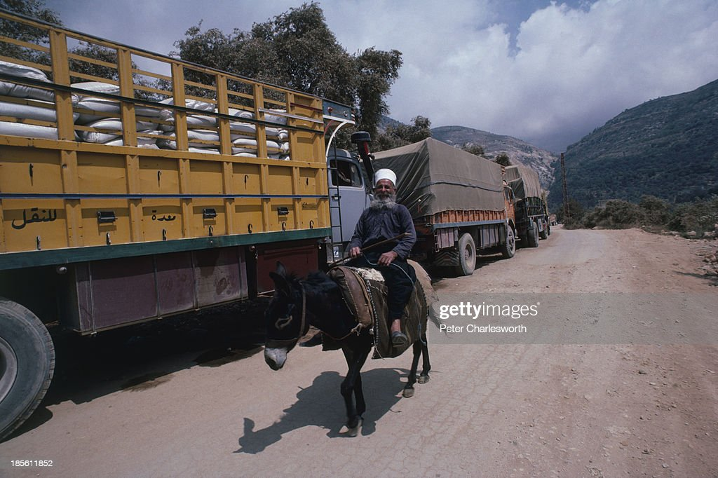 An old (probably druze) man rides his donkey past trucks ...