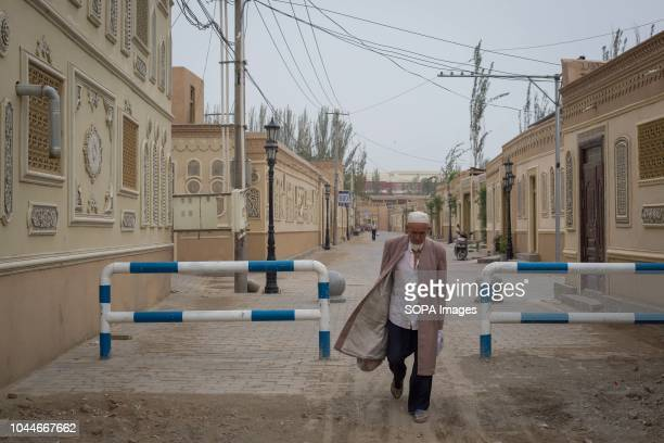 An old man seen walking on the streets of Keriya surrounded by newly houses in the Hotan Prefecture Xinjiang Uyghur Autonomous Region in China...