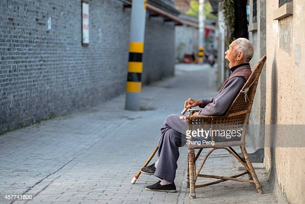 An old man sits alone in an ancient alley In China there are more than 200 million old people of over 60 years old at present which accounts for 15%...