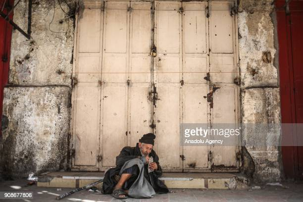 An old man sits at a street during general strike in Gaza City Gaza on January 22 2018 Many shopkeepers can not open their shops due to the worsening...