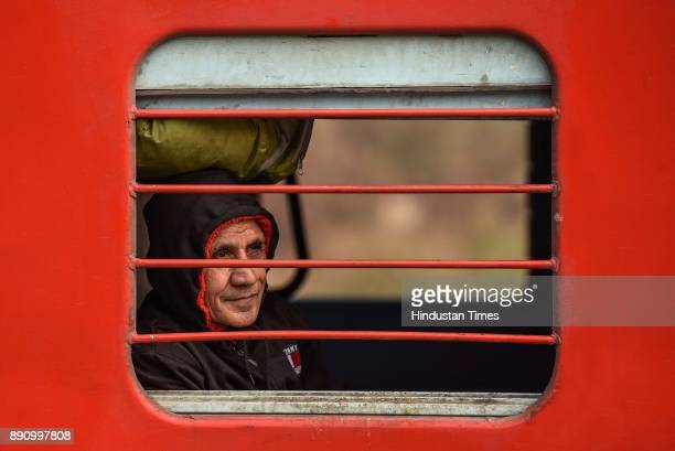 An old man sits inside a passenger train on a cold morning at Nizamuddin Railway station on December 12 2017 in New Delhi India