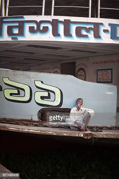 An old man sits smoking on a ferry at the Sadarghat ferry terminal Dhaka Bangladesh