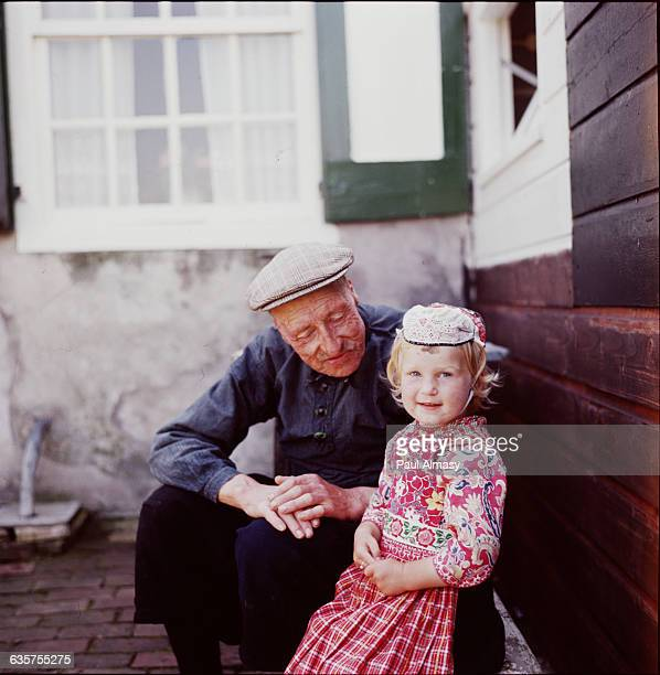 An old man sits with a young girl who wears a traditional embroidered dress on the Dutch island of Marken