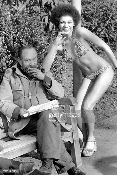 An old man sitting on a park bench reading his newspaper next to a model in bikini February 1975 7501132007