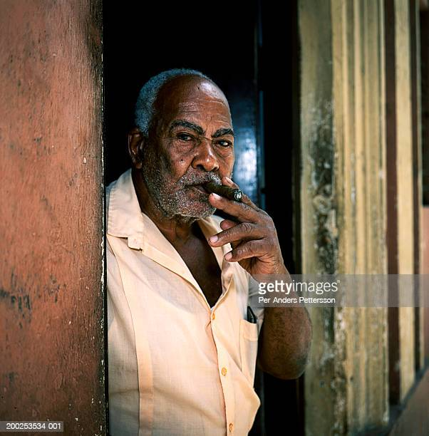 An old man smoking a cigar looks out of a door in Old Havana, Cuba