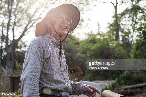 An old man standing and smiling in his garden