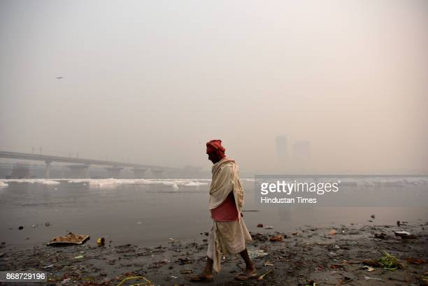 An old man walks on the banks of Yamuna as people of the city woke up to a hazy morning with monitoring stations across the national capital...
