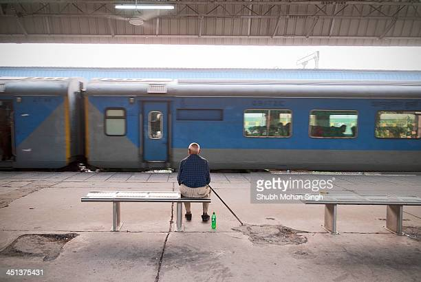An old man watches the Shatabdi express train carrying his loved ones depart the Chandigarh Railway Station.