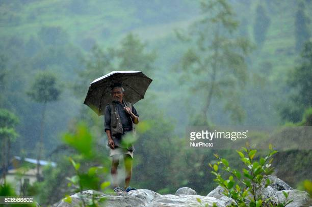 An old man watching as Crane managing road that occurred due to the heavy rainfall at Timbu Khola Aambathan Melamchi Nepal on Wednesday August 09...