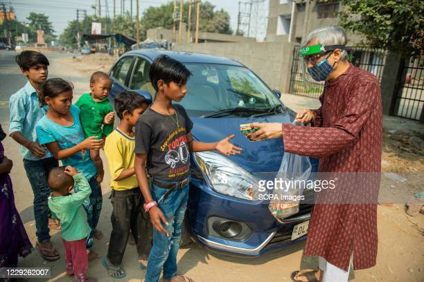 An old man wearing a facemask is seen distributing biscuit packets to homeless children and families during Navaratri one of the prominent Hindu...