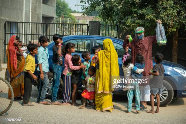 An old man wearing a faceshield is seen distributing biscuit packets to homeless children and families during Navaratri one of the prominent Hindu...
