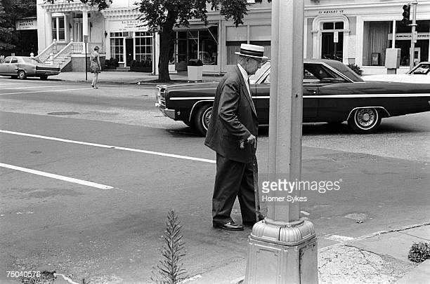 An old man wearing a Panama straw hat crossing Nassau street in Princeton New Jersey 1969
