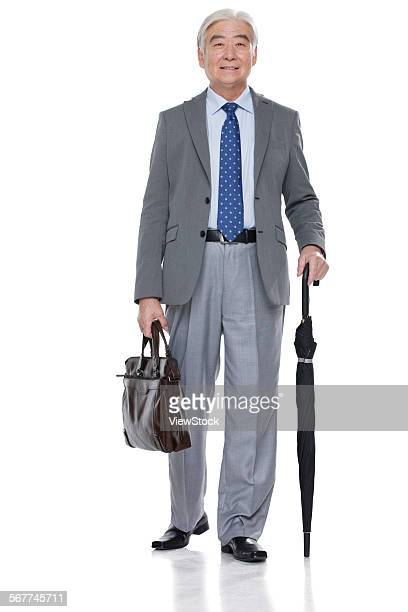An old man with a briefcase and umbrella