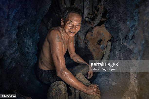An old man with charcoal making