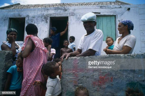 An old man women and children in front of a house in Sao Pedro | Location Sao Pedro Sao Vicente Island Cape Verde