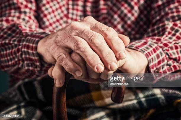 an old man's arthritic hands holding onto a cane - rheumatism stock pictures, royalty-free photos & images