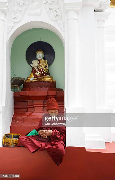 An old monk is sitting in front of a shrine at the Shwedagon Pagoda on June 16 2016 in Yangon Myanmar