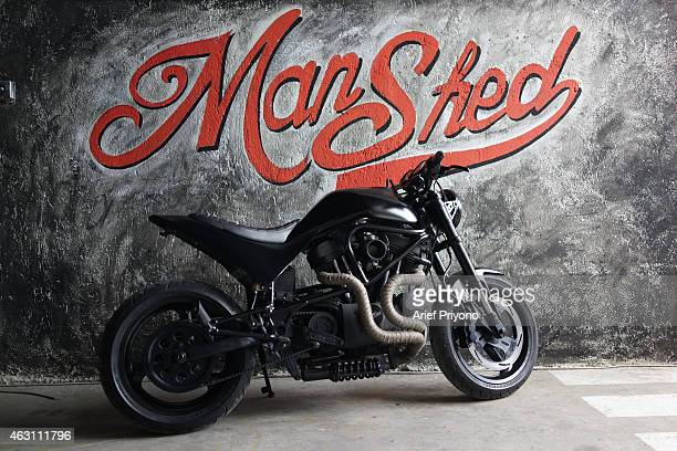 An old motorcycle parked as a display in ManShed Cafe Sanur The ManShed cafe in Sanur Bali is themed on an old style garage and is full of...