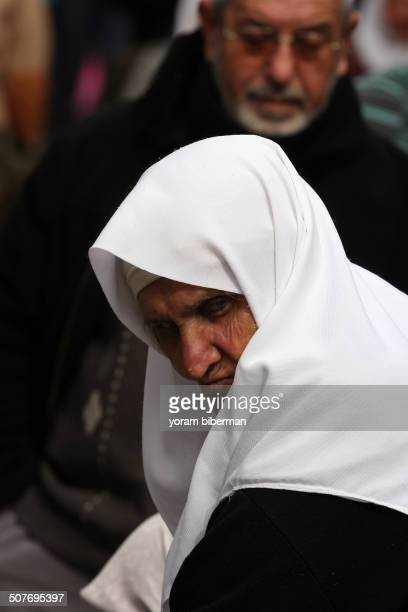CONTENT] An old Muslim lady with a shining white hijab looking downward in an harsh angry facial expression You see her from the shoulders up and...