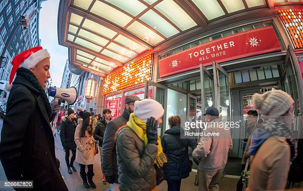 An Old Navy employee entices shoppers into the store in the Herald Square shopping district in New York on Thursday, November 27, 2014. December...