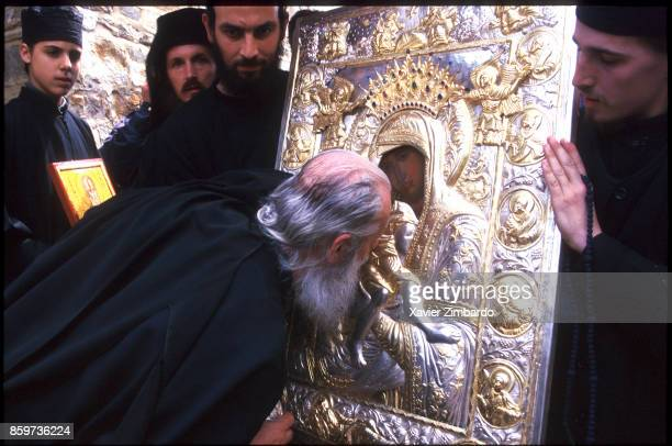 An old Orthodox Monk kissing an icon of the Virgin Mary and Jesus Christ during a procession at Easter on April 27 1997 near Karyes the seat of the...