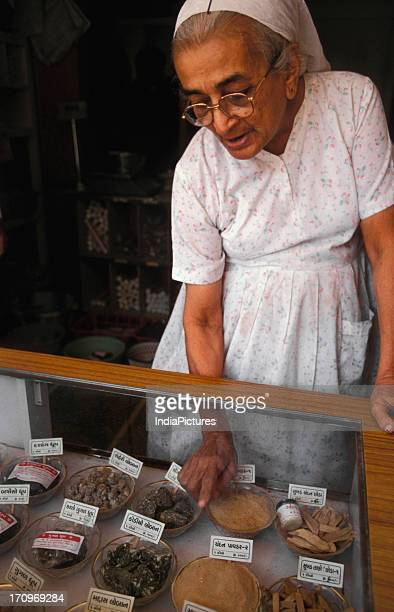 An old Parsi lady selling incense at a shop in Ahemdabad Gujarat India