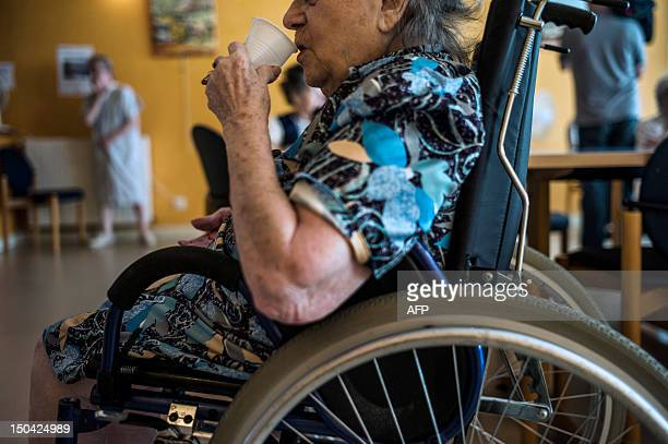An old person in a wheelchair is pictured drinking a glass of water on August 17 in Lormes eastern France during the visit of Social Affairs and...