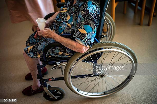 An old person in a wheelchair is pictured with a glass of water on August 17 in Lormes eastern France during the visit of Social Affairs and Health...