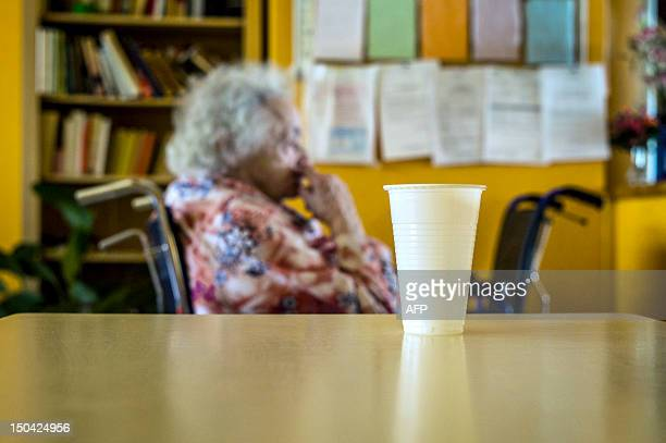 An old person is pictured seatting near a glass of water on August 17 in Lormes eastern France during the visit of Social Affairs and Health Minister...