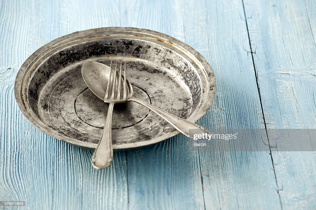 An old plate with fork and spoon : Stock Photo